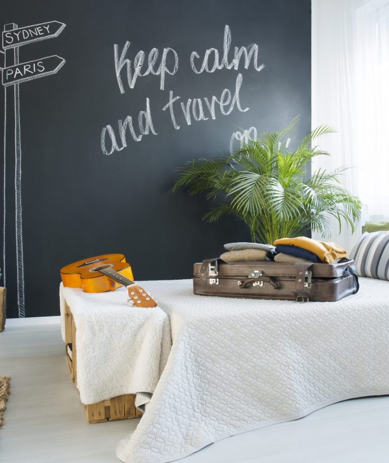 Bed in modern travel-themed bedroom with blackboard wall