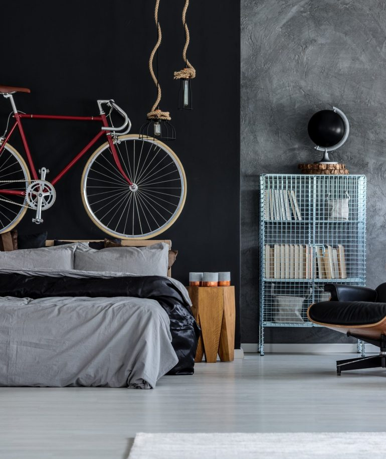 Modern designed bedroom with red bicycle above the bed