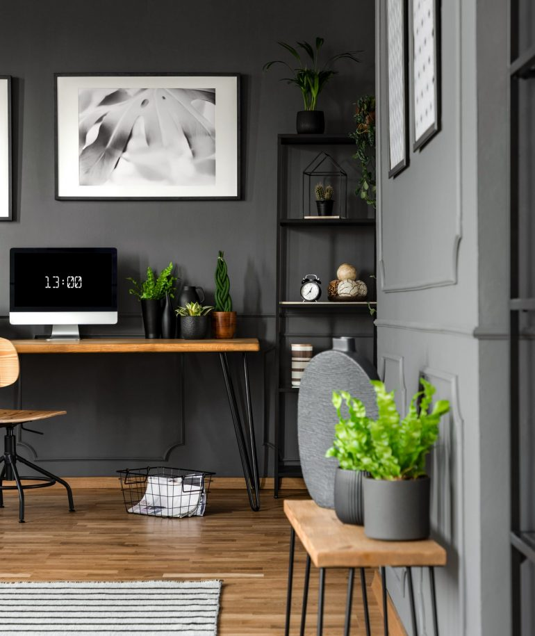 Plants on wooden table in grey home office interior with posters above desk with computer monitor