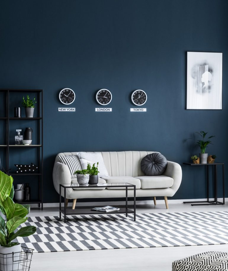 White sofa, coffee table, clocks on the grey wall and striped rug in a modern living room interior