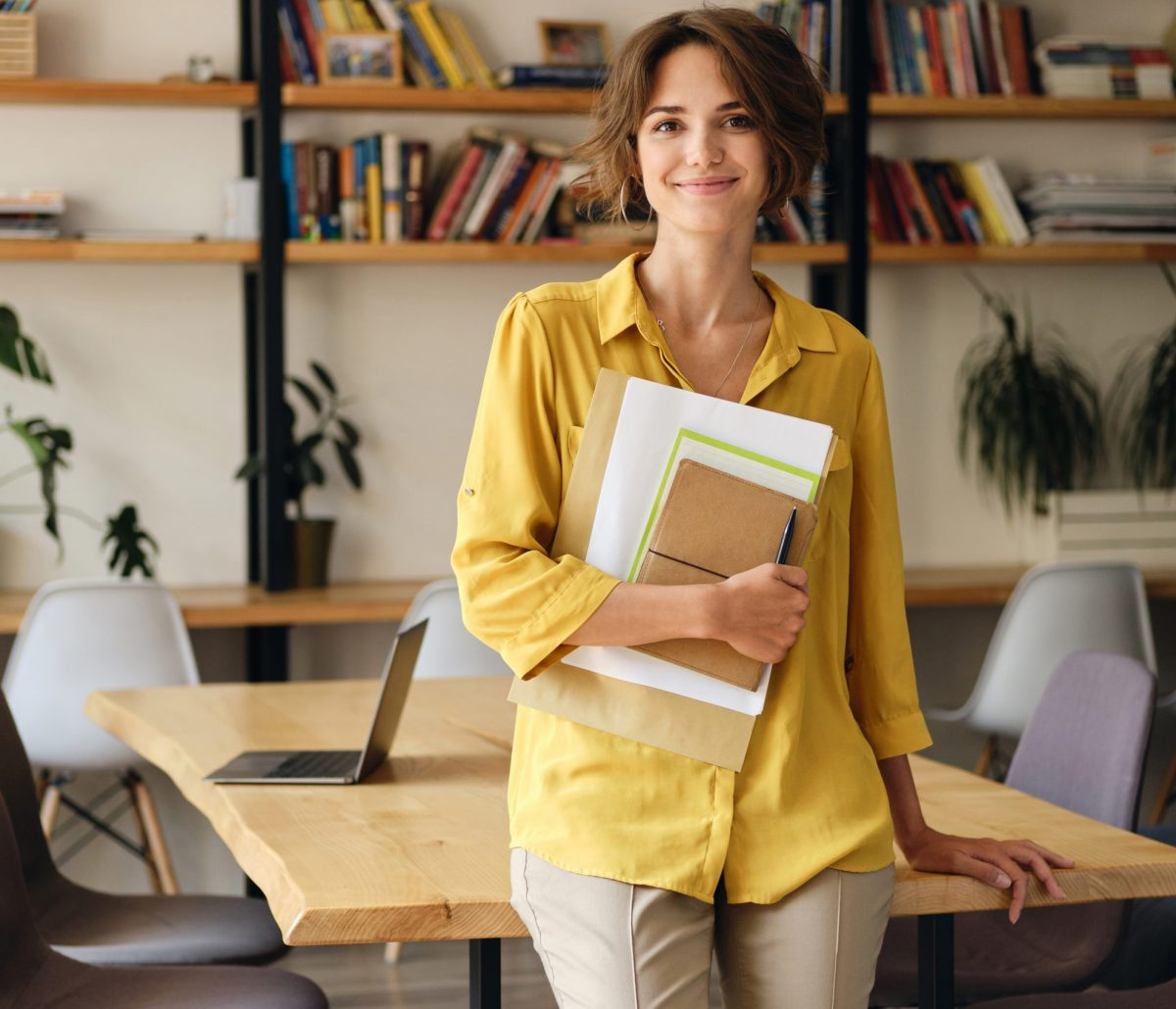 Young smiling woman in yellow shirt leaning on desk with notepad and papers in hand happily looking in camera in modern office