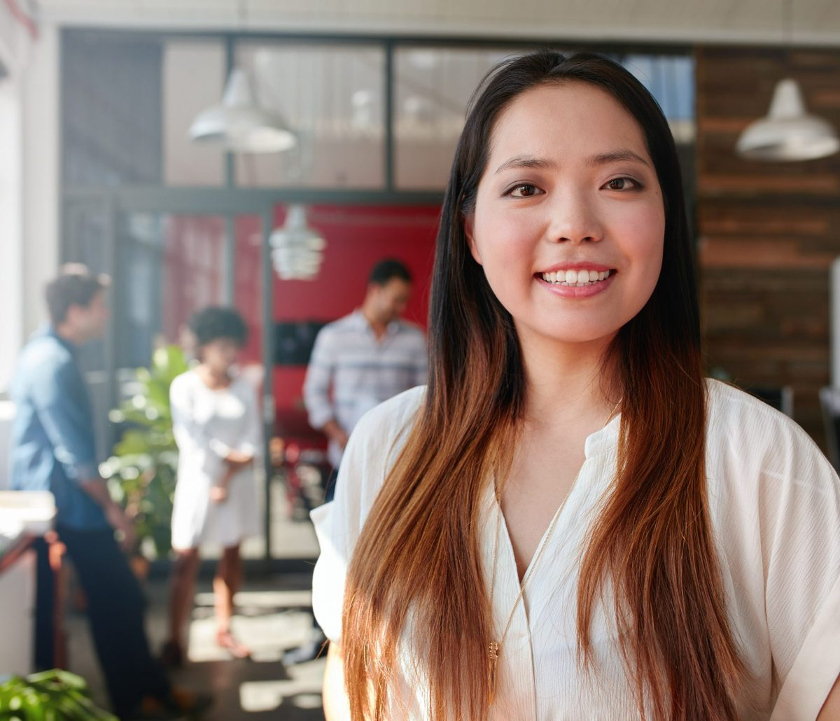 Smiling young businesswoman looking at camera and her colleagues are standing in the background. Young asian female creative professional.